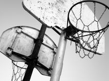 Basketball Hoops. Slanted black and white image of basketball hoops and backboards on playground royalty free stock images