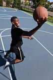 Basketball Layup. A young basketball player driving to the hoop with some fancy moves. Shallow depth of field Royalty Free Stock Images