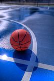 Basketball at midcourt. A basketball sitting near the line on a blue outdoor basketball court Stock Image