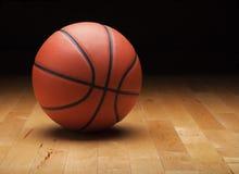 Basketball mit dunklem Hintergrund auf hölzernem Turnhallenboden Lizenzfreie Stockfotos