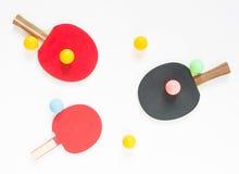 Basketball mit Metallflügeln Rote und schwarze Tischtennisschläger und -bälle Flache Lage, Draufsicht lizenzfreie stockfotografie