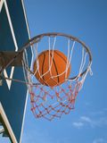 Basketball in the net. A ball in the basket net with a clear blue sky behind stock photos