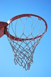 Basketball net. An orange & white basketball net with a clear blue sky background Royalty Free Stock Images