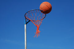 Basketball in the net. Basketball scoring a goal through the net against a blue sky background Stock Photography