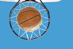 Basketball in the net against. Clear blue skies - concept of a successful endeavor Stock Images