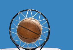 Basketball in the net against clear blue skies Stock Photos
