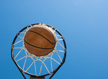 Basketball in net agaisnt blue skies. Successful end to hard work - abstract concept of reaching one's goals, with copy space Royalty Free Stock Image