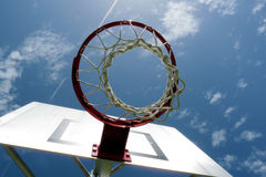 Basketball net and backboard. Low angle view of basketball hoop, net and backboard, blue sky and cloudscape in background Royalty Free Stock Images