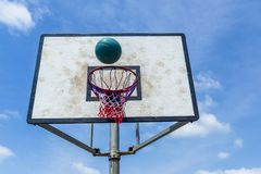 Basketball Net Ball Outdoors. Basketball blue ball flight towards board and net against sky outdoor court Royalty Free Stock Images