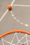 Basketball net and goal. With a view over the hoop of the court below and a basketball on the tarmac, shallow dof stock photography