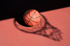 Basketball and net shadow. A Basketball and net shadow on a red court Stock Photography