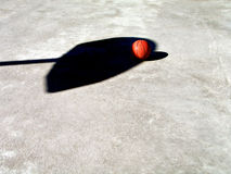 Basketball and Net Shadow. Shot of a basketball on the playground court. The shadow is goal and net royalty free stock photography
