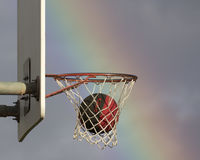 Basketball in net. Basketball slipping through the net with brilliant rainbow background Royalty Free Stock Images