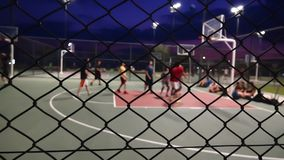 The basketball at night. Stock video is a great piece of video that contains men playing basketball outdoors on a court fenced in with wires stock footage