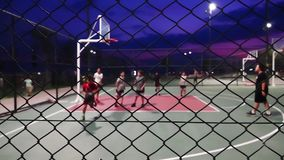 Basketball At Night. The Basketball At Night stock video is a great piece of video that contains men playing basketball outdoors on a court fenced in with wires stock video footage