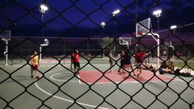 The basketball at night. Stock video is a great piece of video that contains men playing basketball outdoors on a court fenced in with wires stock video footage
