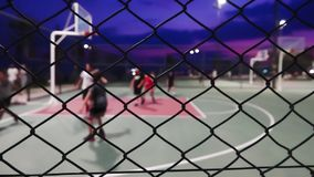 Basketball At Night. The Basketball At Night stock video is a great piece of video that contains men playing basketball outdoors on a court fenced in with wires stock video