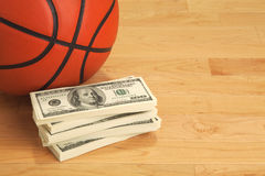 Basketball and one hundred dollar bills on wooden court floor Stock Photo