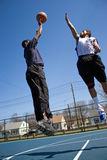 Basketball One On One. A young basketball player shooting the basketball and his opponent trying to block it Stock Photo