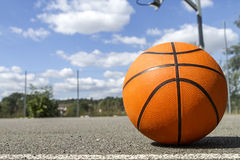 Basketball on an outdoor court on a bright sunny day Stock Photos
