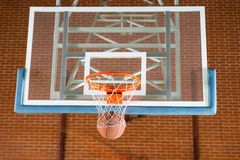 Basketball passing through the goal post. Basketball passing through the net on the goal post in front of a transparent backboard on an indoor court royalty free stock photo