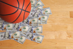 Basketball on pile of one hundred dollar bills Royalty Free Stock Photography