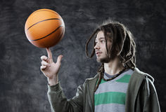Basketball player. Portrait of young man spinning basketball on finger Stock Photo
