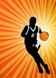 Basketball player on the abstract orange background Stock Photos