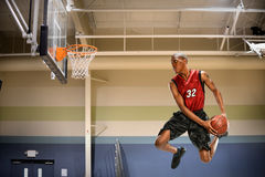Basketball Player in Action. African american basketball player in action in indoor court Stock Images