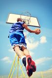Basketball player in action flying high and scoring Royalty Free Stock Photo
