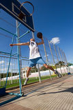 Basketball player is aiming the basket. Young male basketball player is jumping high to slam dunk into the basket Stock Photos