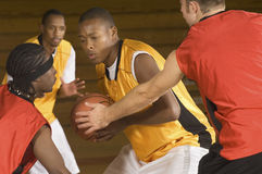 Basketball Player With Ball Being Blocked By Opponents Stock Photo