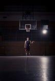 Basketball player, ball bounce, indoors. One young adult man, basketball player posing, ball bounce, indoors dark basketball court Royalty Free Stock Photos