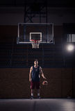 Basketball player, ball bounce, indoors. One young adult man, basketball player posing, ball bounce, indoors dark basketball court Royalty Free Stock Image