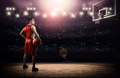 Basketball player with ball. The imaginary basketball arena is modelled and rendered Stock Images