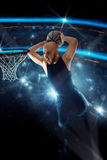 Basketball player in black jersey makes a slam dunk in the game Stock Image