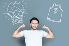 Smiling basketball player looking strong and showing his muscles. Basketball player. Cheerful hardworking sportsmen enjoying his progress in playing basketball Stock Images