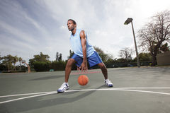 Basketball player dribbling the ball Stock Images