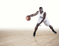 Basketball Player Dribbling On A Hardwood Court Stock Image