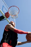 Basketball Player Dunking. A young basketball player under the rim going for a reverse slam dunk.  Shallow depth of field with stronger focus on the goal Royalty Free Stock Photo