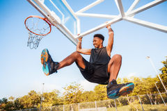 Basketball player hangs on the rim.sport outfit,sport competitions Royalty Free Stock Photos