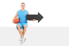 Basketball player holding an arrow seated on panel Stock Photography