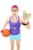 Basketball player holding a golden trophy Stock Photos