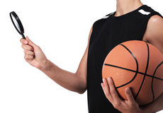 Basketball player holding a magnifying glass. Photography of a basketball player holding a magnifying glass stock photo