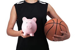 Basketball player holding a piggy bank Royalty Free Stock Photos