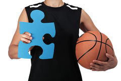 Basketball player holding a puzzle piece Royalty Free Stock Photography