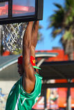 Basketball Player Holding Rim. Basketball player holding the net at Venice Beach, CA famous boardwalk and birth of Dog Town Stock Photo