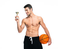 Basketball player holding winners cup. Happy basketball player holding winners cup isolated on a white background royalty free stock photos