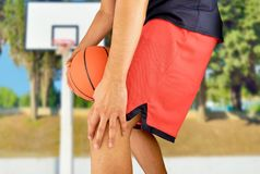 Basketball player with injured knee. Shot of a young basketball player with an inflamed knee at outdoors Stock Image