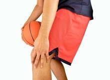 Basketball player with injured knee. Studio shot of a young basketball player with an inflamed knee stock image